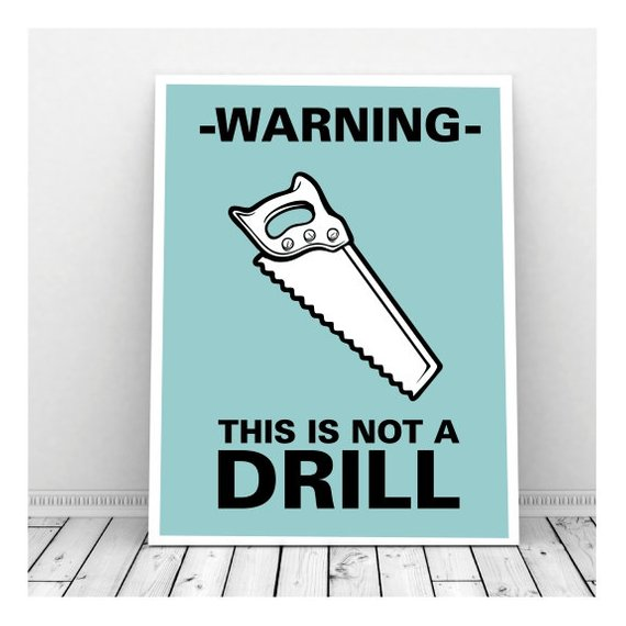 "A sign again a wall on a wood-plank floor that says ""Warning - This is Not a Drill"""